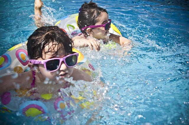 Dos niñas bañándose en el agua con flotadores divertidos y gafas de sol rosas ¿Recuerdas cuánto disfrutabas de niñ@?